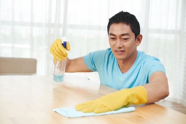 Azjatycki mężczyzna rozpyla stół i czyści z płótnem w domu w gumowych rękawiczkach