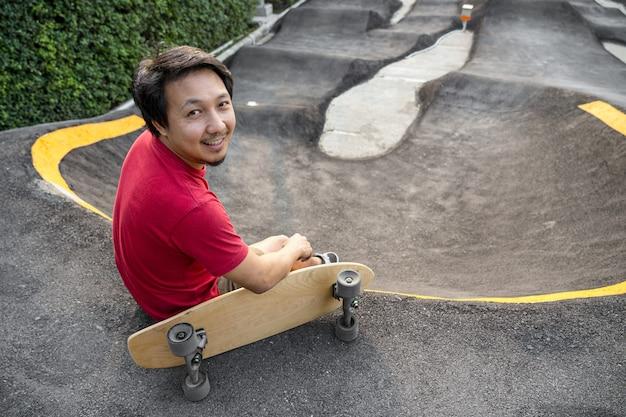 Azjatycki mężczyzna siedzący z deską surfingową lub deskorolką w skate parku pumptrack, gdy czas wschodu słońca