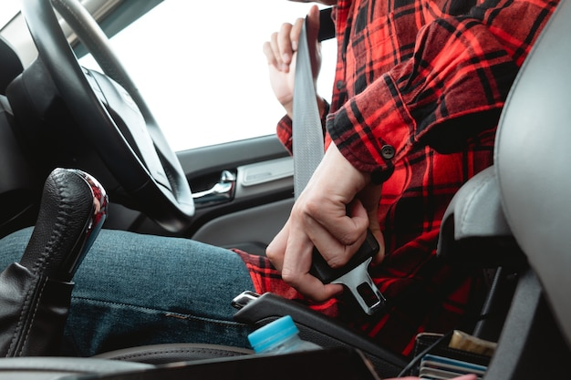 Azjatycki mężczyzna siedzi na foteliku samochodowym zapinając pas bezpieczeństwa przed jazdą dla bezpieczeństwa, zapobiegając niebezpieczeństwu wypadku na drodze.