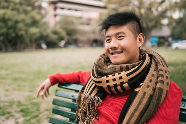 Azjatycki mężczyzna siedzi na ławce w parku.