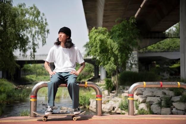 Azjatycki mężczyzna siedzi po deskorolce