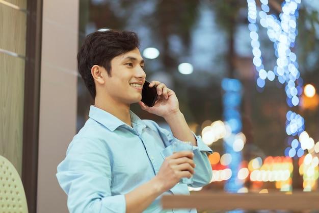 Azjatycki mężczyzna siedzi samotnie w kawiarni
