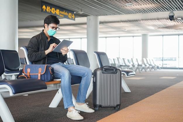 Azjatycki mężczyzna siedzi samotnie w salonie do oczekiwania na wejście na pokład formularza linii lotniczych w strefie odlotów lotniska