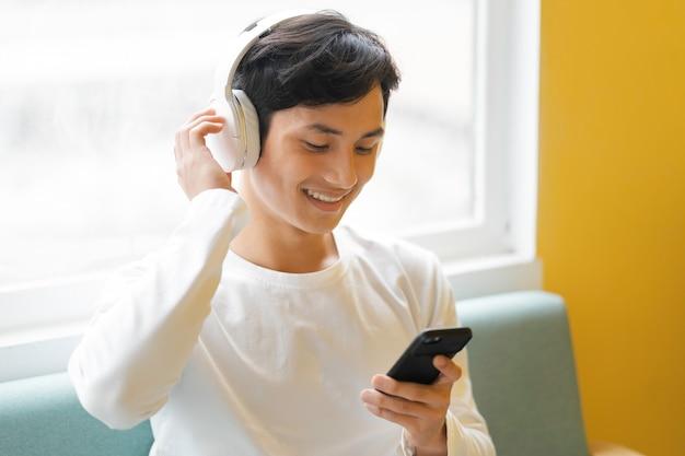 Azjatycki mężczyzna siedzi, słuchając muzyki