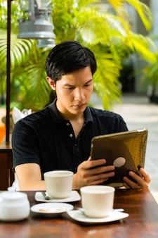 Azjatycki mężczyzna siedzi w barze lub kawiarni na świeżym powietrzu