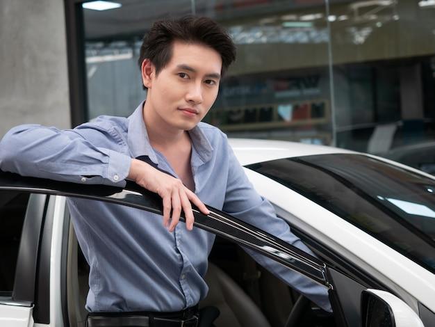Azjatycki mężczyzna siedzi w nowym samochodzie i pokazuje kluczyki do samochodu. młodego atrakcyjnego mężczyzna salonu siedzący samochodowy samochód przyglądający otwarte okno out.