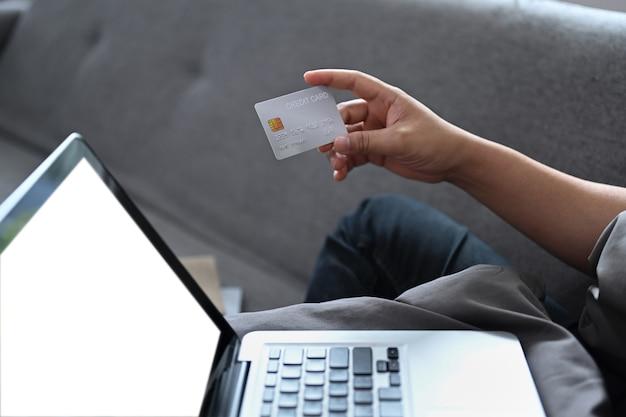 Azjatycki mężczyzna siedzi w salonie i po rozmowie wideo na komputerze przenośnym.