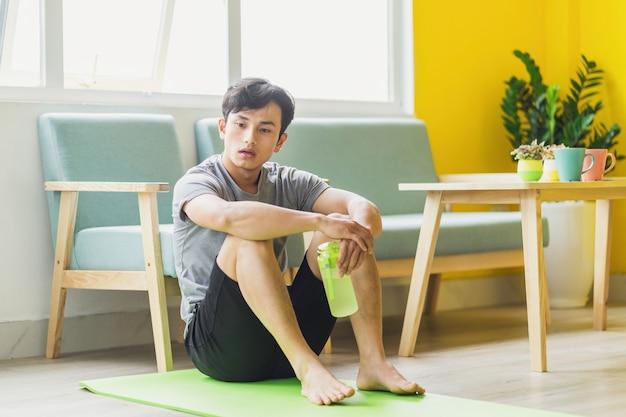 Azjatycki mężczyzna siedzi w stanie spoczynku po ćwiczeniach