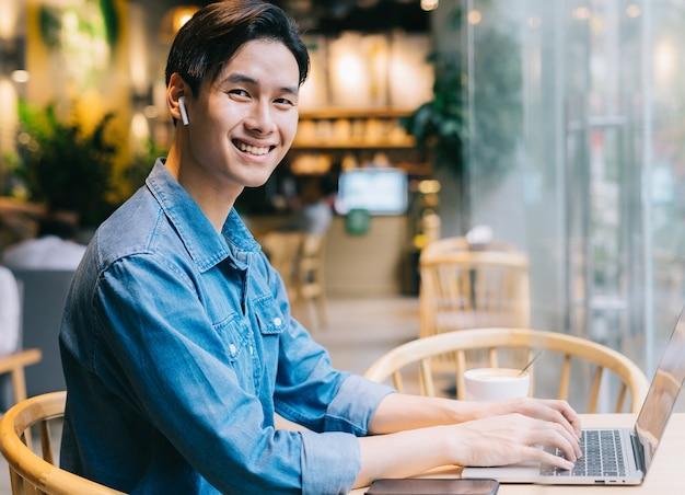 Azjatycki mężczyzna siedzi za pomocą laptopa w kawiarni