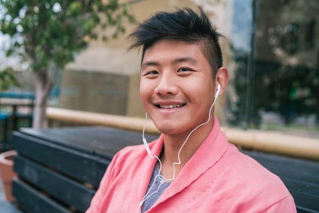 Azjatycki mężczyzna słucha muzyka z słuchawkami.