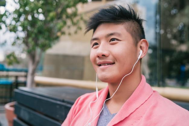 Azjatycki mężczyzna słucha muzyka z słuchawkami