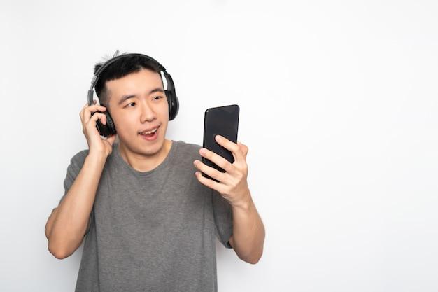 Azjatycki mężczyzna słuchanie muzyki ze smartfona i przeglądanie internetu na białym tle