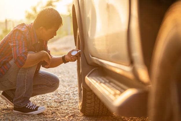 Azjatycki mężczyzna sprawdza ciśnienie powietrza jego samochód