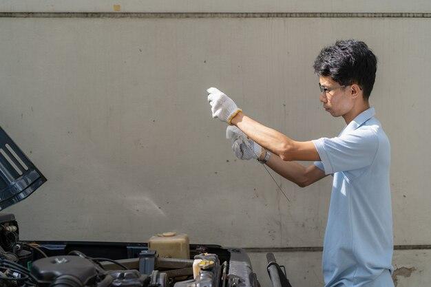 Azjatycki mężczyzna sprawdza w górę parowozowego smaru oleju zakończenia up.