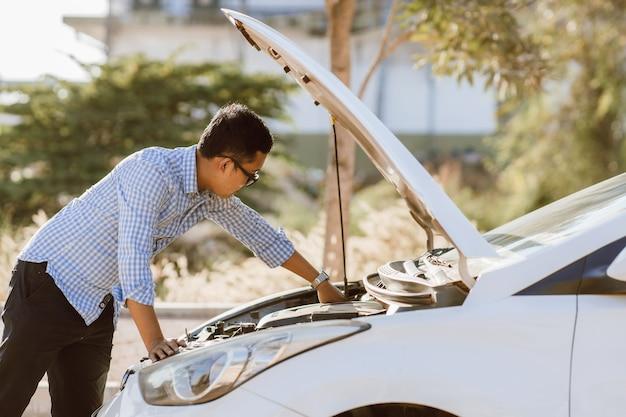 Azjatycki mężczyzna stoi przed samochodem, sprawdzając stan samochodu po zepsutym samochodzie. zepsuty samochód na drodze. pogotowie ma uszkodzony samochód.
