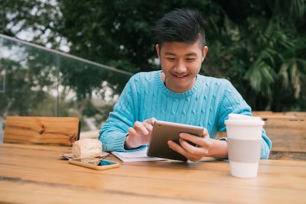 Azjatycki mężczyzna studiuje w sklep z kawą