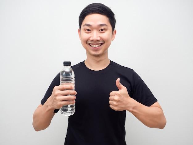 Azjatycki mężczyzna trzyma butelkę wody i kciuk w górę szczęśliwy uśmiech, wesoły mężczyzna z butelką wody