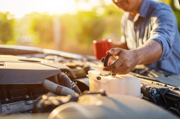 Azjatycki mężczyzna trzyma czerwoną filiżankę i sprawdza silnik jego samochód w ranku