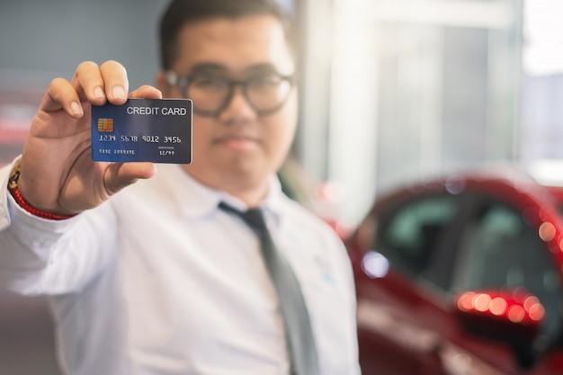 Azjatycki mężczyzna trzyma kredytową kartę dla samochodu zamazywał bokeh tła zakupy marketingu cyfrowego
