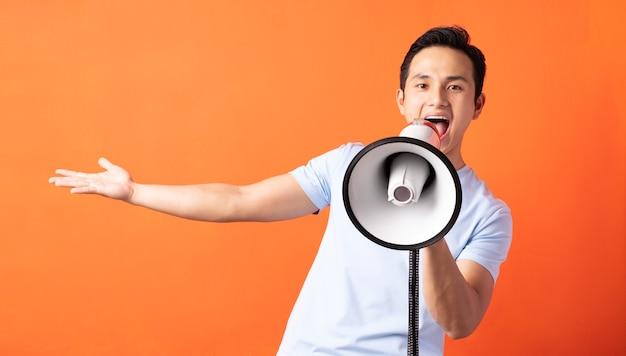 Azjatycki mężczyzna trzyma megafon i krzyczy