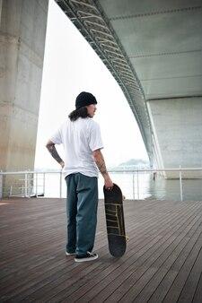 Azjatycki mężczyzna trzymający deskorolkę