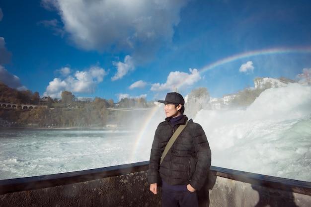 Azjatycki mężczyzna turysta z rheinfall, szwajcaria