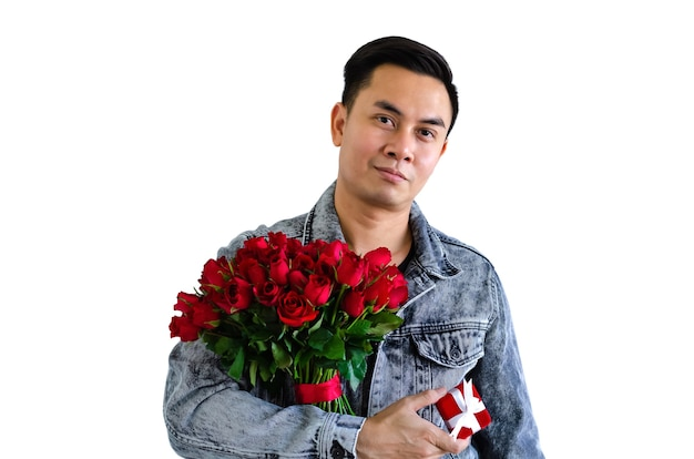 Azjatycki mężczyzna ubrany w dżinsową kurtkę, trzymając bukiet czerwonych róż i czerwone pudełko na białym tle na białym tle na rocznicę lub walentynki koncepcja.