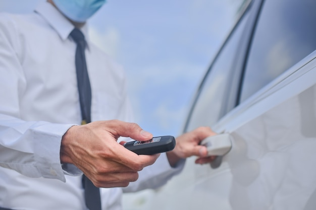 Azjatycki mężczyzna ubrany w maskę medyczną i trzymając klucz do otwierania drzwi samochodu