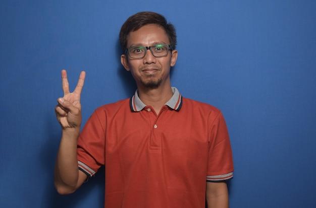 Azjatycki mężczyzna ubrany w pomarańczową koszulkę dorywczą pokazujący palce robiące znak zwycięstwa z numerem dwa