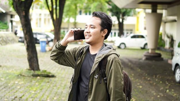 Azjatycki mężczyzna ubrany w torbę podczas telefonu