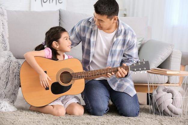 Azjatycki mężczyzna uczy swoją córeczkę grać na gitarze w domu