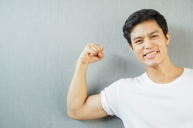 Azjatycki mężczyzna uśmiech z pokazaniem przedramienia bicepsa do dobrego zdrowia i silnej koncepcji ciała