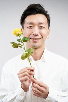 Azjatycki mężczyzna uśmiecha się z żółtym kwiatem róży