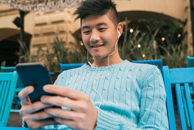 Azjatycki mężczyzna używa jego telefon komórkowego z słuchawkami.