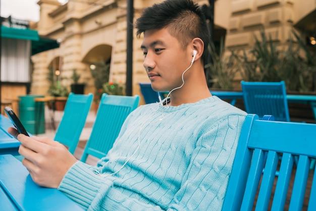 Azjatycki mężczyzna używa jego telefon komórkowego z słuchawkami