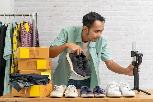 Azjatycki mężczyzna używa mądrze telefon komórkowego bierze żywych sprzedawanie buty online