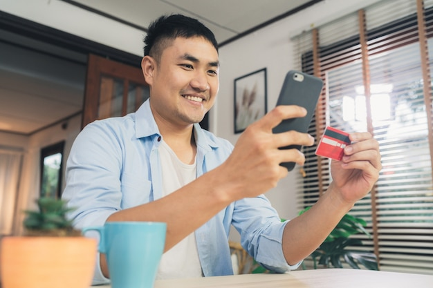 Azjatycki mężczyzna używa smartphone dla online zakupy i kredytowej karty w internecie przy żywym pokoju domem