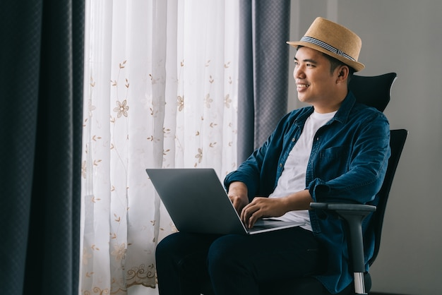 Azjatycki mężczyzna używa swojego laptopa do pracy online przy oknie, koncepcja pracy z domu