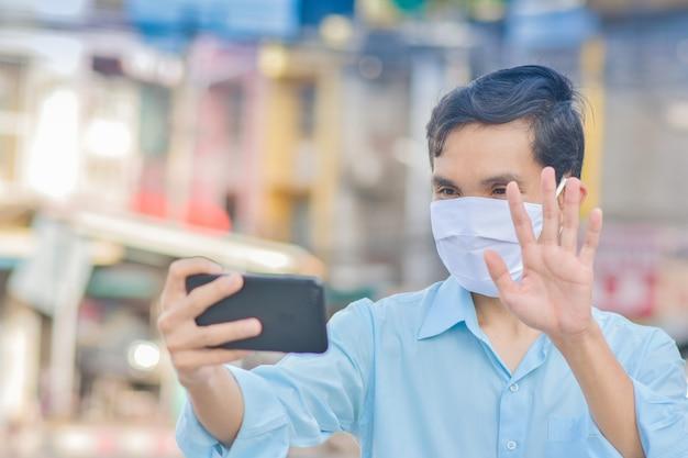 Azjatycki mężczyzna używać maski na twarz wideokonferencja na ulicy w mieście nowa normalna koncepcja dystansowania społecznego