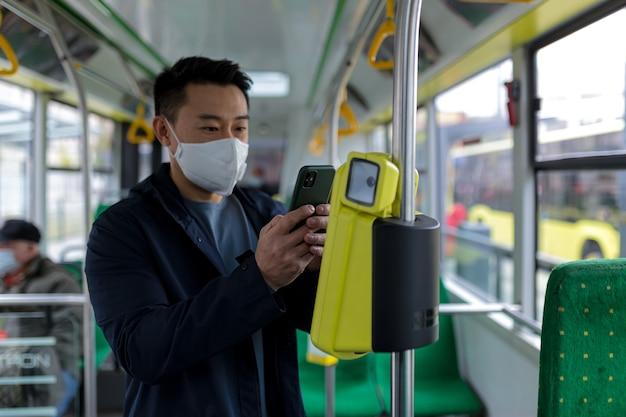 Azjatycki mężczyzna w autobusie transportu publicznego w ochronnej masce medycznej kupuje bilet elektroniczny przez telefon, pasażer w pustym autobusie
