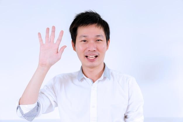 Azjatycki mężczyzna w białej koszuli macha ręką do komunikacji