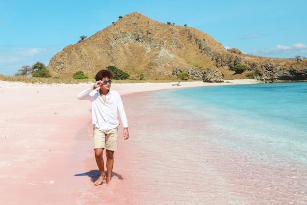 Azjatycki mężczyzna w białej koszuli spacerujący po różowej piaszczystej plaży, ciesząc się letnim czasem