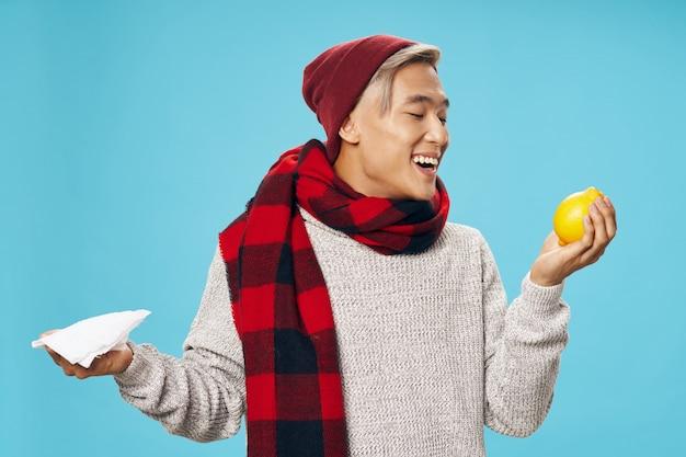 Azjatycki mężczyzna w ciepłych zimowych ubraniach pozuje na barwionej ścianie