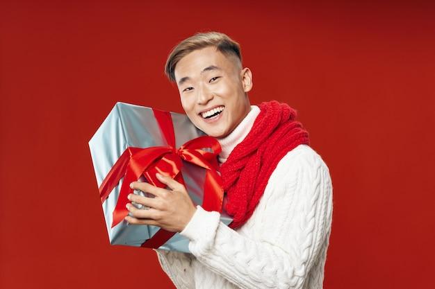 Azjatycki mężczyzna w ciepłych zimowych ubraniach pozuje przestrzeń na barwionej przestrzeni