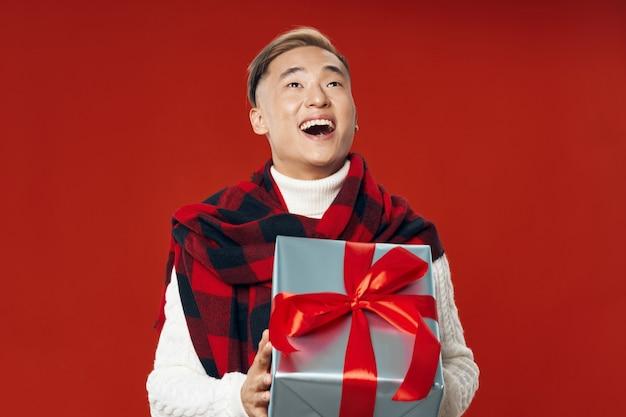 Azjatycki mężczyzna w ciepłych zimowych ubraniach pozuje w studiu na barwionym