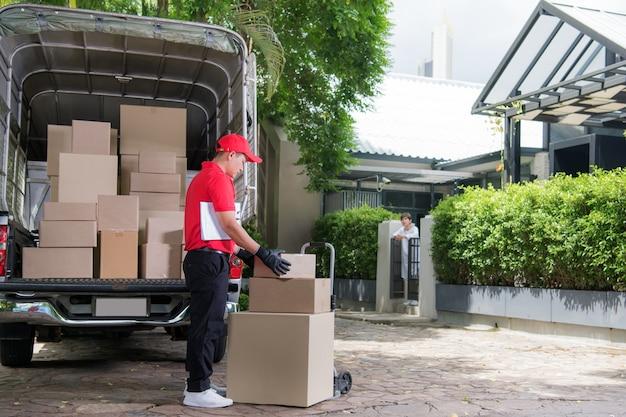 Azjatycki mężczyzna w czerwonym mundurze dostawy paczek do odbiorcy kobiety w domu
