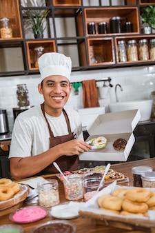 Azjatycki mężczyzna w kapeluszu szefa kuchni, siedząc w kuchni