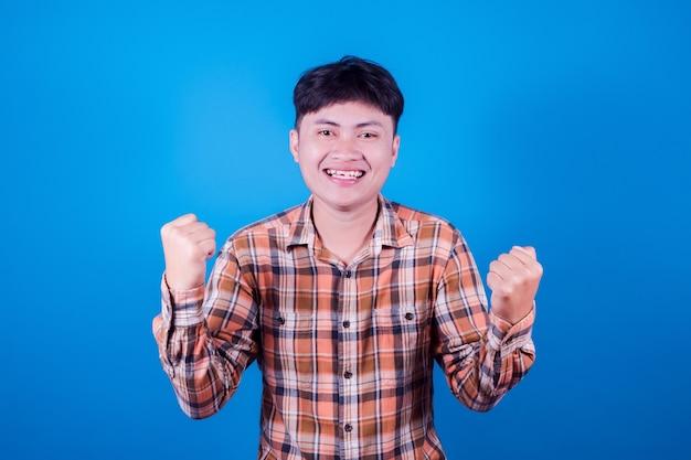 Azjatycki mężczyzna w koszuli w paski, uśmiechający się na niebieskim tle, radosny wyrażając świętujący zwycięstwo dobrej nowiny