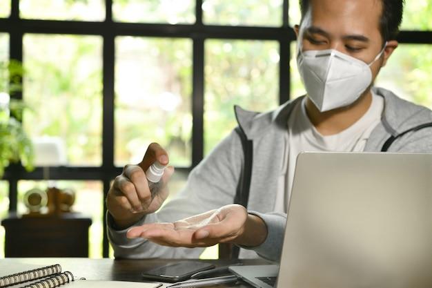 Azjatycki mężczyzna w kwarantannie i dystansie społecznym, noszący maskę chirurgiczną i czyszczący dłonie środkiem do dezynfekcji żelem alkoholowym podczas pracy z domu podczas pandemii koronawirusa covid-19
