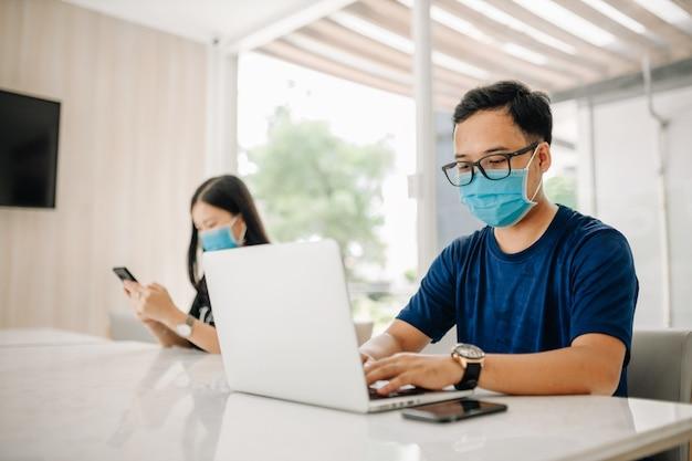 Azjatycki mężczyzna w masce i korzystający z laptopa w biurze lub klasie w celu zapobiegania wirusowi covid-19.